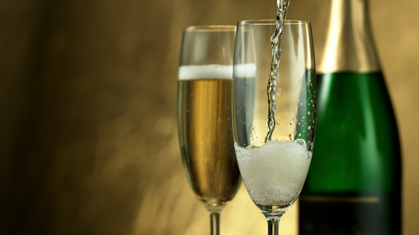 Super slow motion of pouring Champagne wine into glasses, closeup view. Filmed on high speed cinema camera, 1000fps | Shutterstock HD Video #1038006455