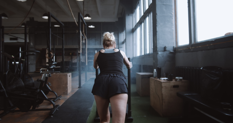Willpower and motivation, camera follows young athletic woman pushing heavy training sled training in gym slow motion. | Shutterstock HD Video #1038039905