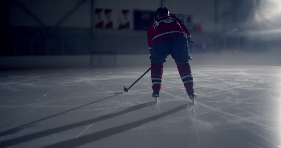 Close up of hockey player skating in dramatically lit hockey rink skating and stick handling then taking a slap shot and scoring a goal  | Shutterstock HD Video #1038217865