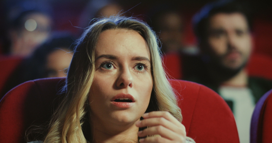 Close up of the young Caucasian blond attractive woman watching horror movie in the cinema, closing eyes with a hand as being afraid. | Shutterstock HD Video #1038255665