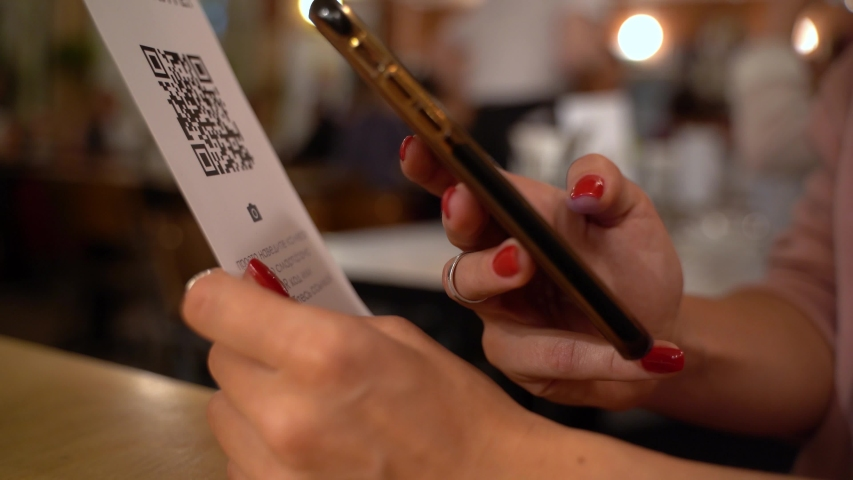Scanning QR code with smart phone. The woman reads the bar code using the application on the smartphone in cafe | Shutterstock HD Video #1038521075