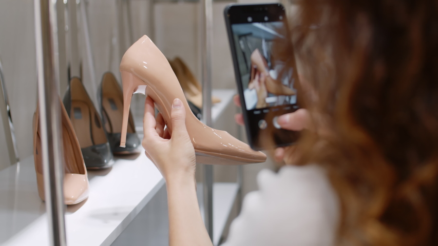 Back view of woman with curly hair standing at rack in shoe shop, holding beige patent leather shoe in her hand and making photo of it using phone