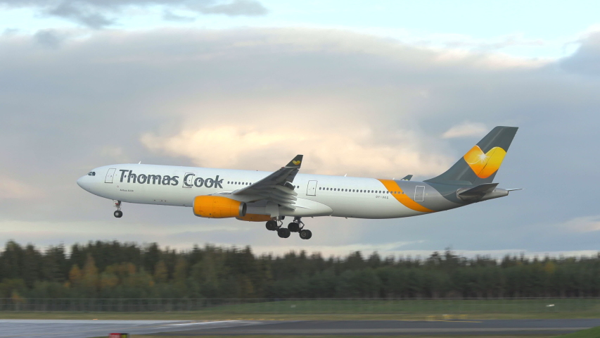 Oslo airport norway - ca october 2019: airplane airbus 330 thomas cook airlines scandinavia landing rear view slow motion panning left late evening sun