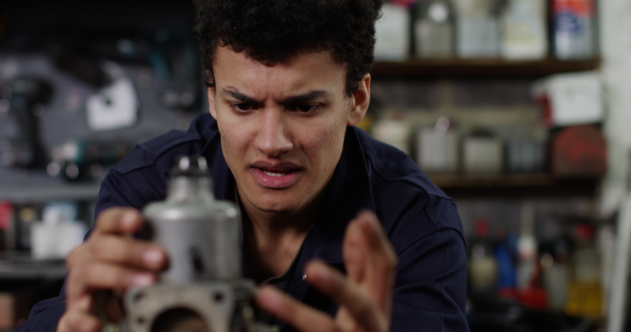 4K Mechanics student with no practical skills looking at camera with exasperation | Shutterstock HD Video #1038626885