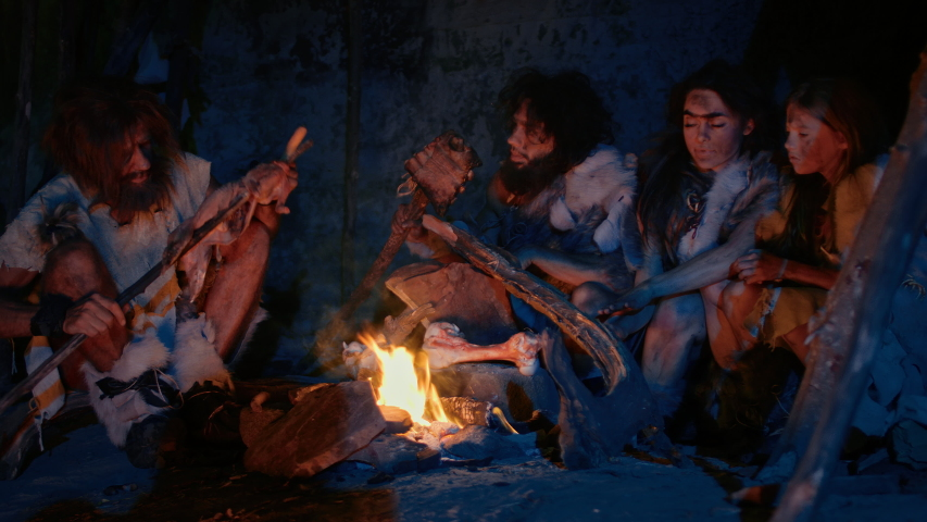 Neanderthal or Homo Sapiens Family Cooking Animal Meat over Bonfire and then Eating it. Tribe of Prehistoric Hunter-Gatherers Wearing Animal Skins Grilling and Eating Meat in Cave at Night | Shutterstock HD Video #1038726965