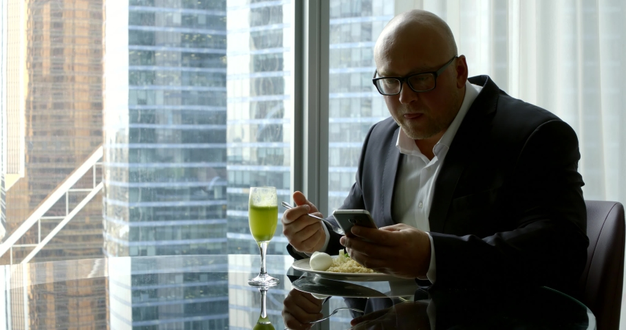Businessman in glasses eats healthy food and simultaneously communicate by video link   Shutterstock HD Video #1038812705