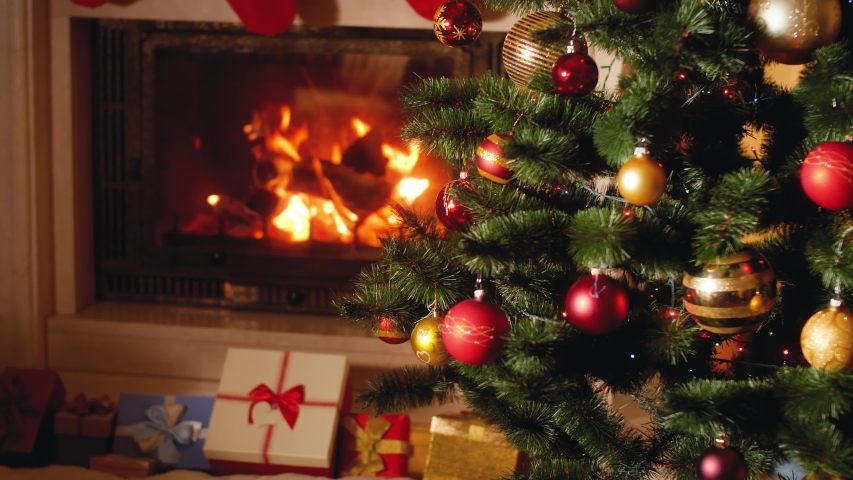 4k footage of big heap of gifts and present next to burning fireplace and glowing Christmas tree in living room on Christmas eve | Shutterstock HD Video #1039189595
