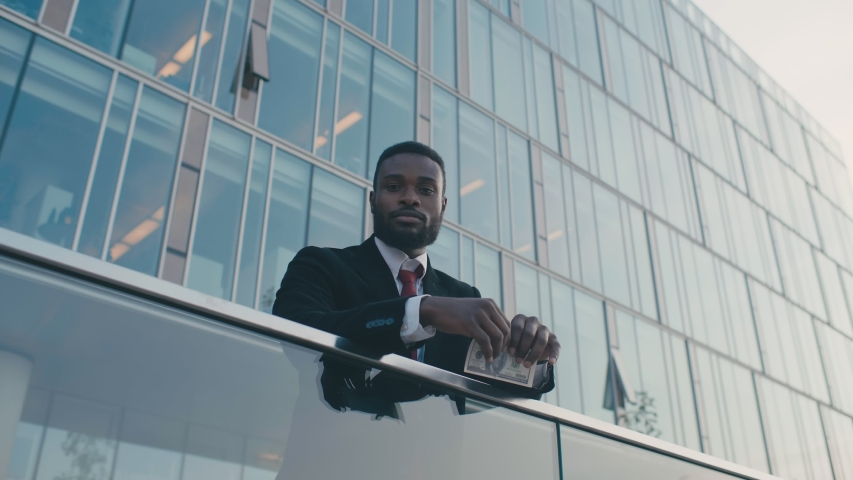 Low ange shot black businessman in formal suit tears money cash money by hands standing in front of glass business center. Arrogant african american person tears dollar banknotes outdoors | Shutterstock HD Video #1039232105