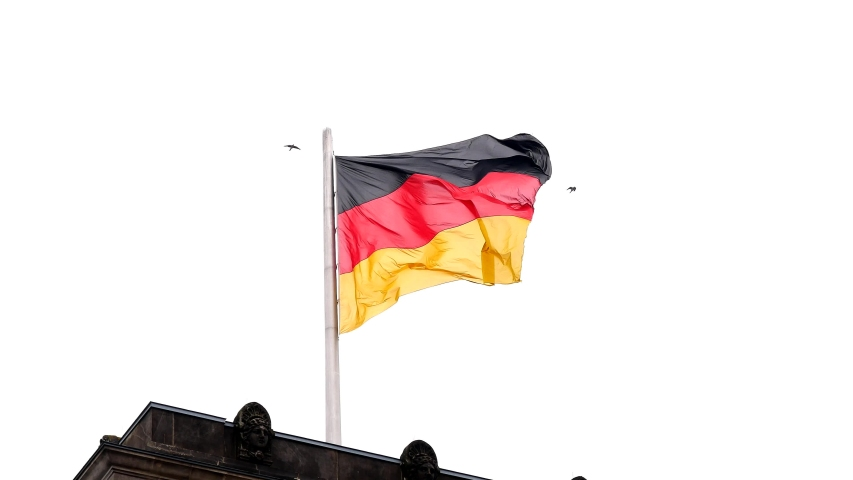 Reichstag (Deutscher Bundestag), flag of Germany on white background. Birds fly over the flag. Famous Reichstag building and tourist place. Closeup. Building roof. Symbolic photo.