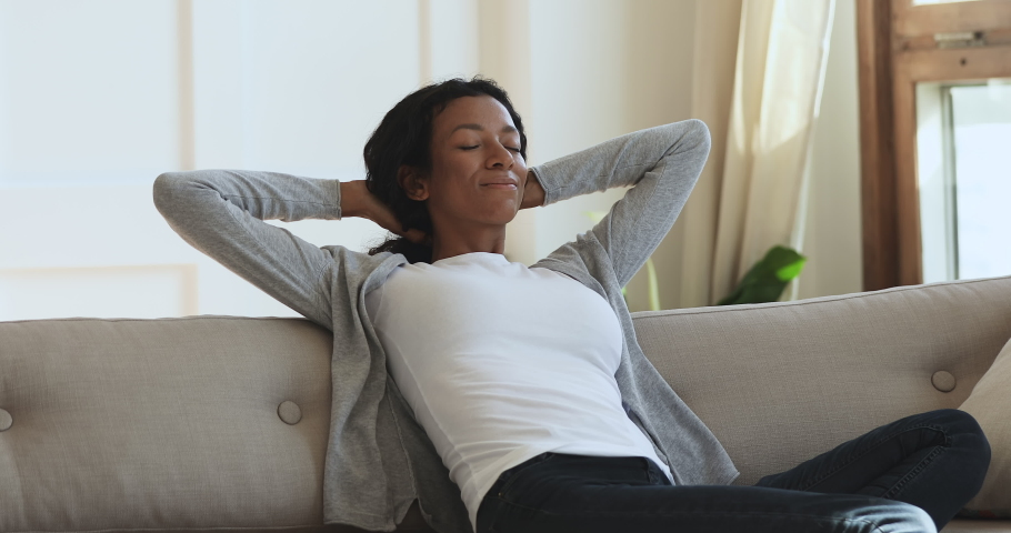 Calm young african american woman relax sit on comfortable sofa holding hands behind head eyes closed, happy mixed race girl rest on couch breathing fresh air enjoy no stress at home in living room | Shutterstock HD Video #1039317695