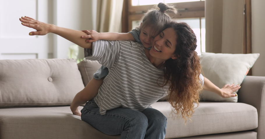 Happy family loving young mum playing piggybacking cute little funny kid daughter sit on couch at home, cheerful mother carrying small child girl on back bonding pretending flying having fun together | Shutterstock HD Video #1039338245