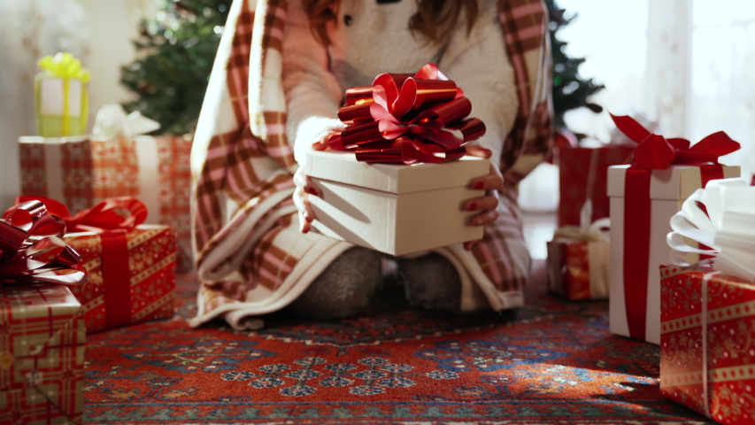 Steadicam shot of girl sitting under the christmas tree and choosing her special christmas gift box. Girl covered with winter warm blanket holding white present box with red ribbon. Glittering | Shutterstock HD Video #1039344845
