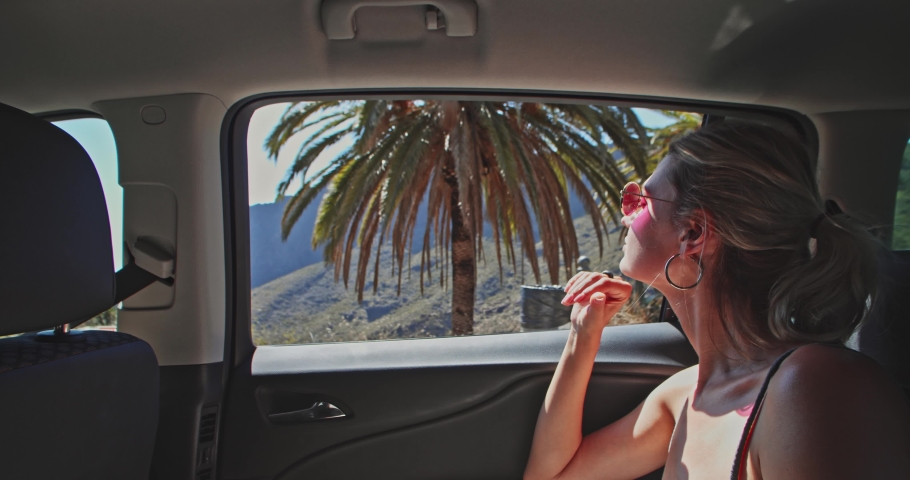 Beautiful girl traveling in the car watching inspiring scenery observing mountains and nature of Masca gorge. Tenerife, Spain. Roadtrip. | Shutterstock HD Video #1039505495