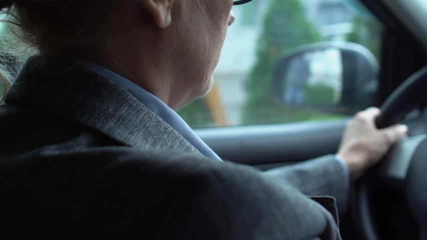 Aged female driver massaging painful neck in car, sedentary lifestyle, health #1039587545