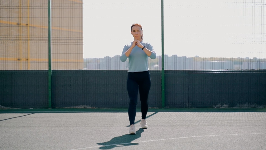 The girl goes in for sports in a fenced area on the street. Fitness exercises on the street. lunges forward. #1039782425