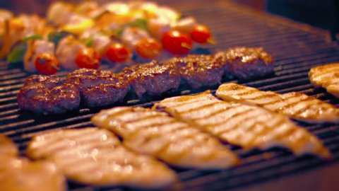 FullHD video - Local. Turkish street vendor cooks kabobs. hamburgers and chicken breasts on a barbecue grill in preparation for the after work crowd.