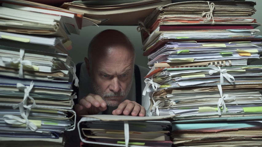Busy office clerk working behind a wall of paperwork, he is sending a man to another office, bureaucracy and administrative process concept | Shutterstock HD Video #1039948385