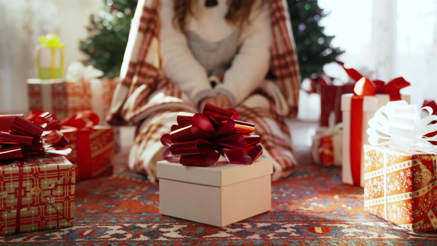 Close-up of christmas gift box with glittering red ribbon under the christmas tree. Girldressed in winter pyjamas with warm blanket sitting under the tree and opening her christmas present. Emotions | Shutterstock HD Video #1039956425