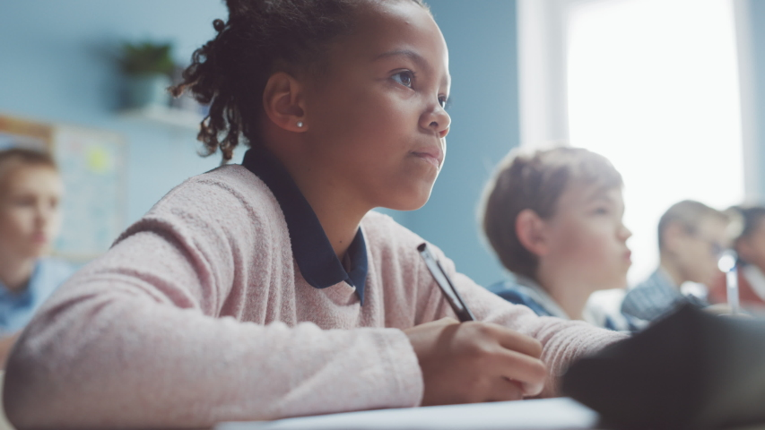 In Elementary School Classroom Brilliant Black Girl Writes in Exercise Notebook, Taking Test. Junior Classroom with Diverse Group of Bright Children Working Diligently and Learning. Low Angle Portrait