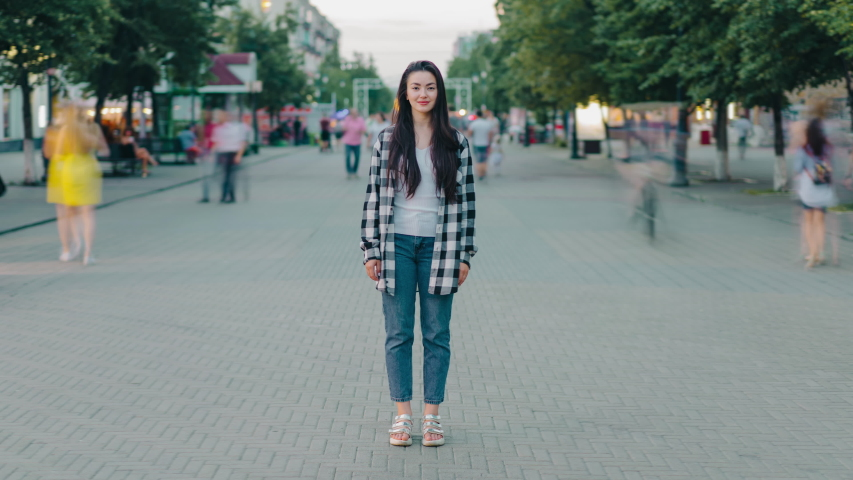 Zoom-in time lapse of beautiful young woman hipster standing outdoors in urban street smiling looking at camera while crowds of people are moving around.