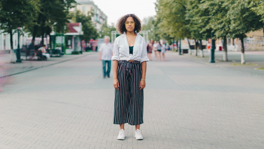 Zoom in time lapse of serious young Afro-American woman in glasses standing outdoors in city looking at camera. Modern youth and casual life concept.