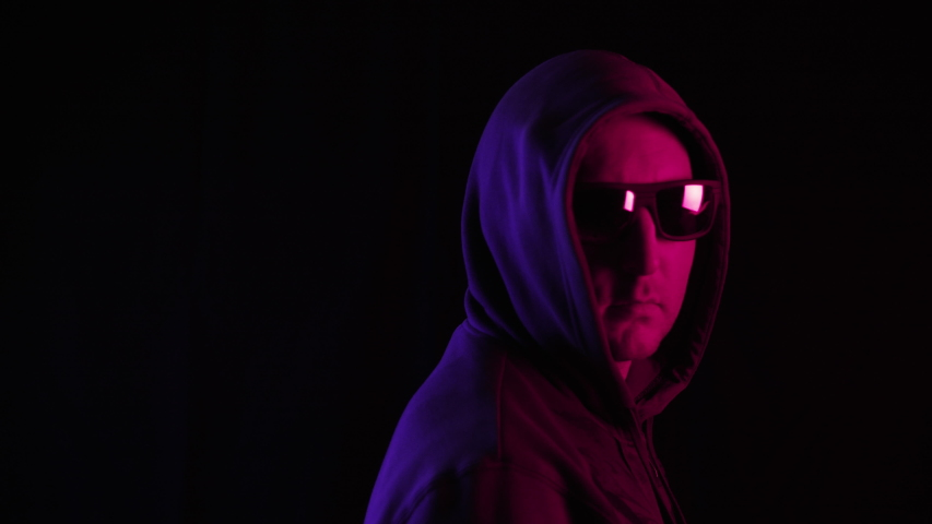 Man in hoodie and sunglasses looking at camera in darkness. Portrait of stylish serious middle aged man wearing hoodie and sunglasses, turning head and looking at camera on black background | Shutterstock HD Video #1040373905