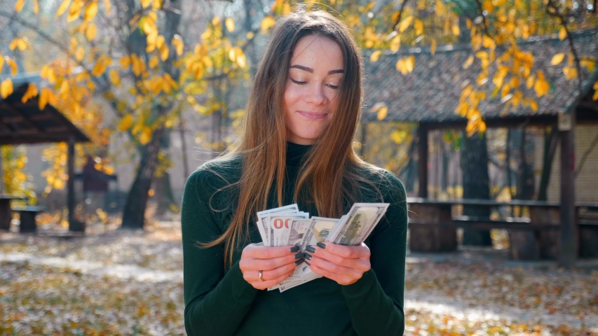 Young attractive brunette woman counting a pack of money and savour. A girl enjoys lot of cash. Huge wealth of money. Employee salary. Cash money payment. Successful business concept. 4K footage. | Shutterstock HD Video #1040532155