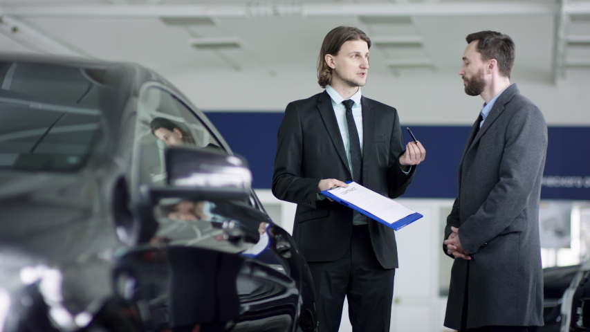 Professional car salesman is telling interested buyer about luxurious car in motor show while man is looking at auto and listening to dealer. They are discussing details of the sold car. Auto business