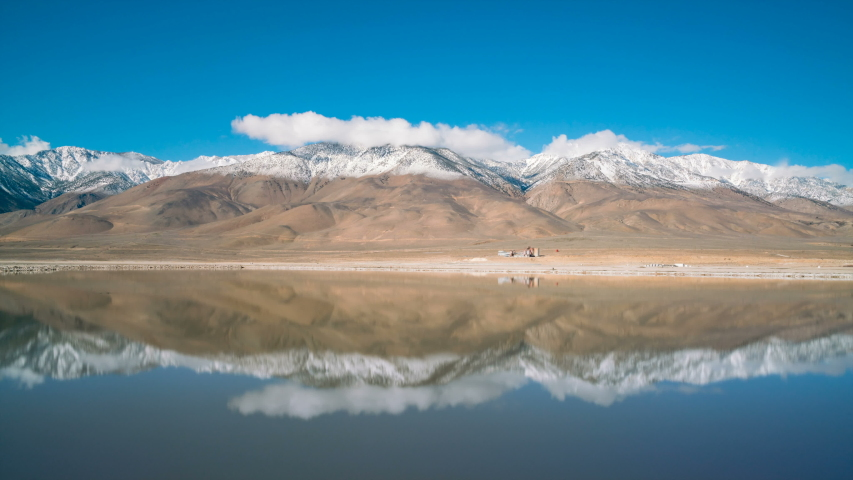 Timelapse long exposure shot of Sierra Nevada mountains reflecting over Owens Lake in California