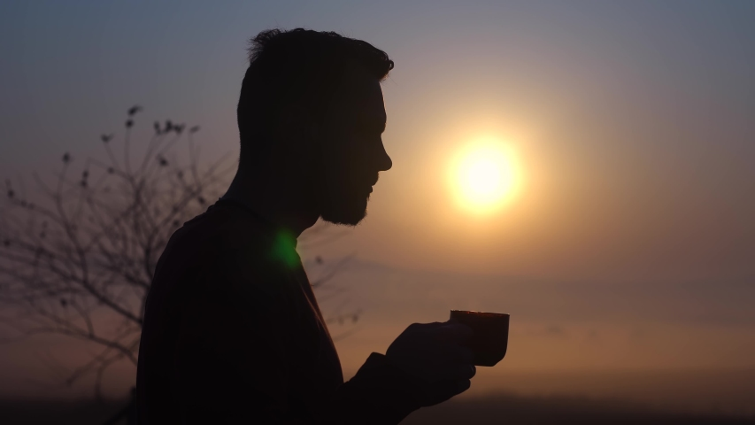 Young bearded guy drinking coffee at dawn. Fragrant coffee in the morning at sunrise. The guy enjoys coffee.The average plan | Shutterstock HD Video #1040701625
