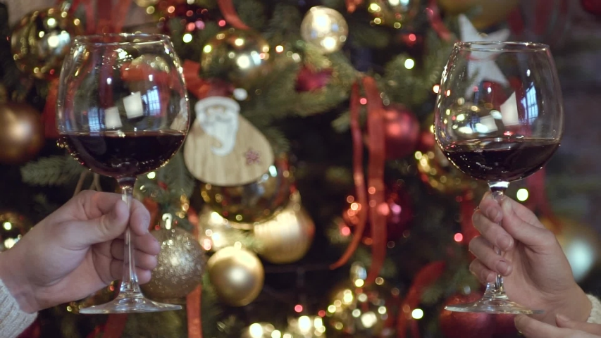 Two glasses of wine close-up on a blurred background, decorated with Christmas toys. Two hands hold glasses for a drink for the holiday. Slow motion video. New Year's and Christmas.