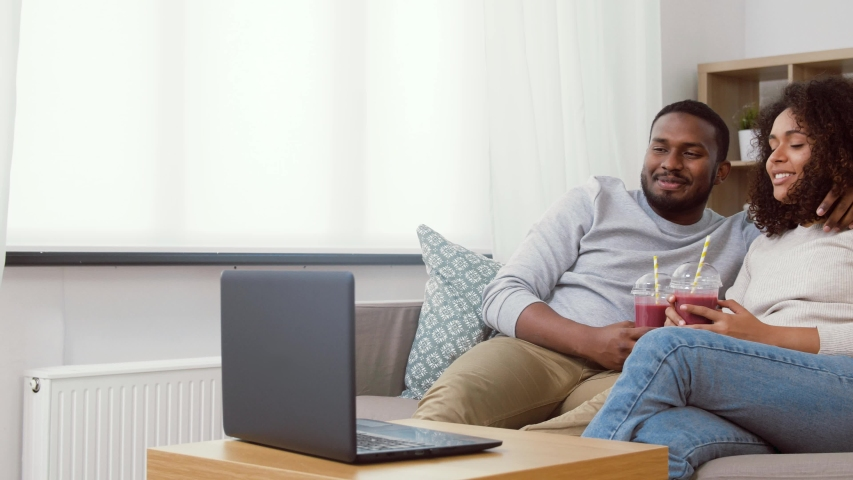 Eating and people concept - happy african american couple with laptop and takeaway smoothie drinks at home | Shutterstock HD Video #1040826695