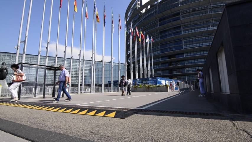 Strasbourg,France.August 2019.The entrance to the modern seat of the European parliament.A row of flagpoles with the flags of the member states of the European Union welcomes those who enter. Tilt mov | Shutterstock HD Video #1040860655