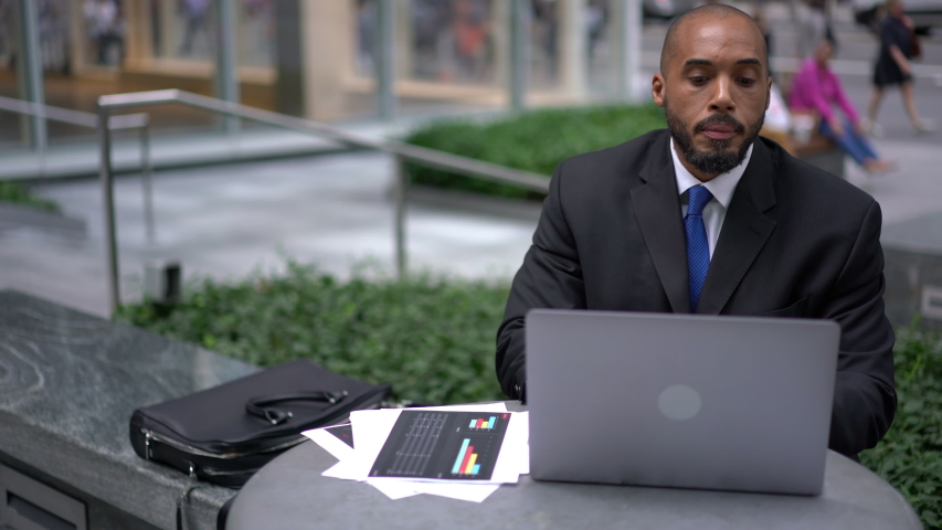 Hispanic man intelligent managing director keyboarding on laptop computer while sitting in cafe terrace, male economist analyzing activities of company via netbook and financial reports  | Shutterstock HD Video #1040954615