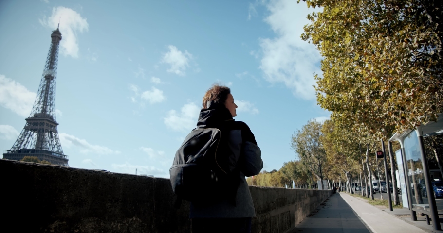 Tourist Girl with a backpack walks the city of Paris, past the Eiffel Tower and the Seine River, and taking photo on smartphone. Wide shot | Shutterstock HD Video #1040971835
