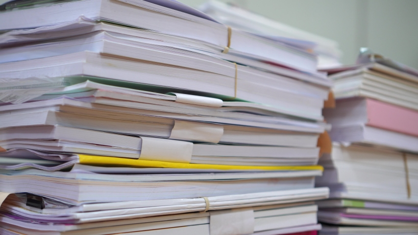 Piles of stack unfinished documents reports files with overwork paperwork on teacher desk office at university. Messy sheet book assessment legal folder at workplace and business tax audit concept | Shutterstock HD Video #1041008915