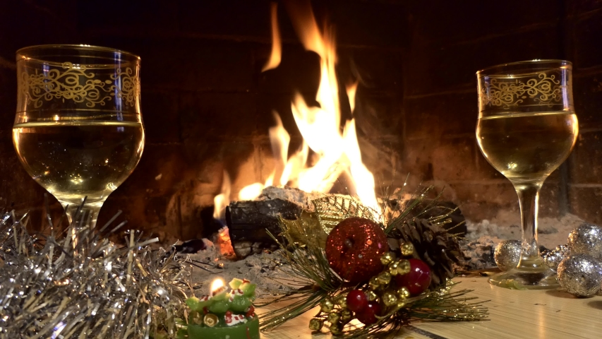 Christmas. New Year. Filled glasses and Christmas decorations stand in front of the fireplace flame. | Shutterstock HD Video #1041101575