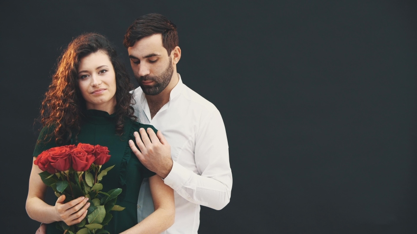 Happy curly girl is holding a bouquet of roses. Romantic young man petting her shoulder. | Shutterstock HD Video #1041108775