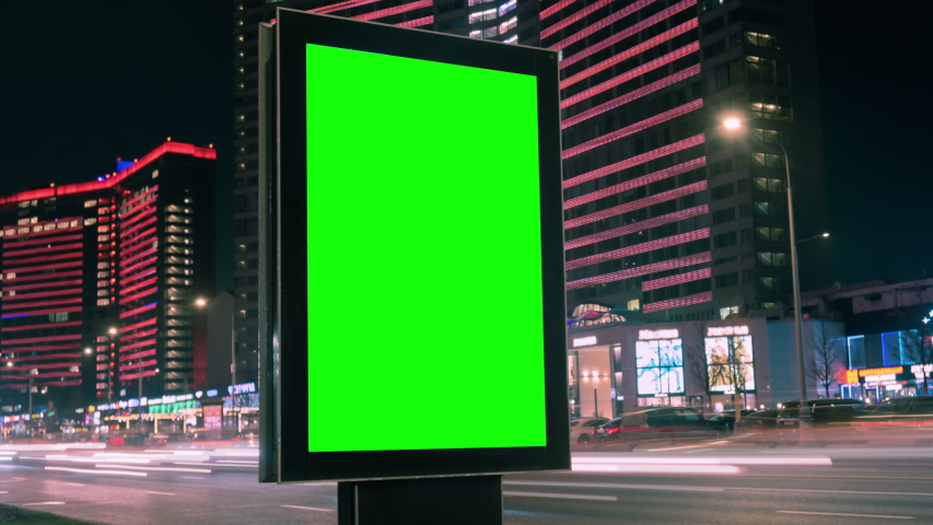 Modern billboard with a green screen on a busy highway with traffic, neon lights, timelapse of traffic at night, Moscow, Russia