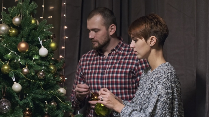 Four young people at home in casual clothes, a two couples decorate the Christmas tree, get ready for the holiday. Reading for party. | Shutterstock HD Video #1041274255