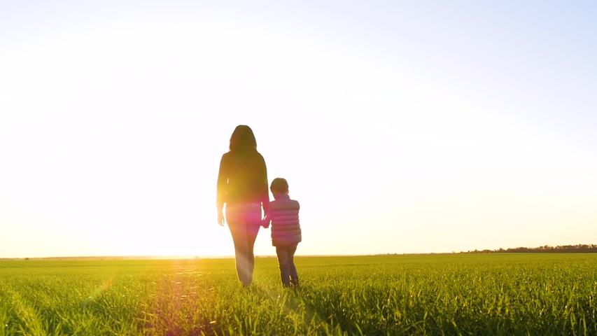 Silhouette of a woman and a child holding hands against the sunset. | Shutterstock HD Video #1041456505