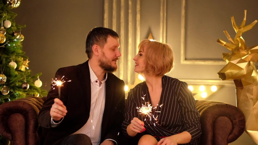 Man and woman wave sparklers and kissing, celebrate the new year holiday. Christmas fun.  | Shutterstock HD Video #1041456925