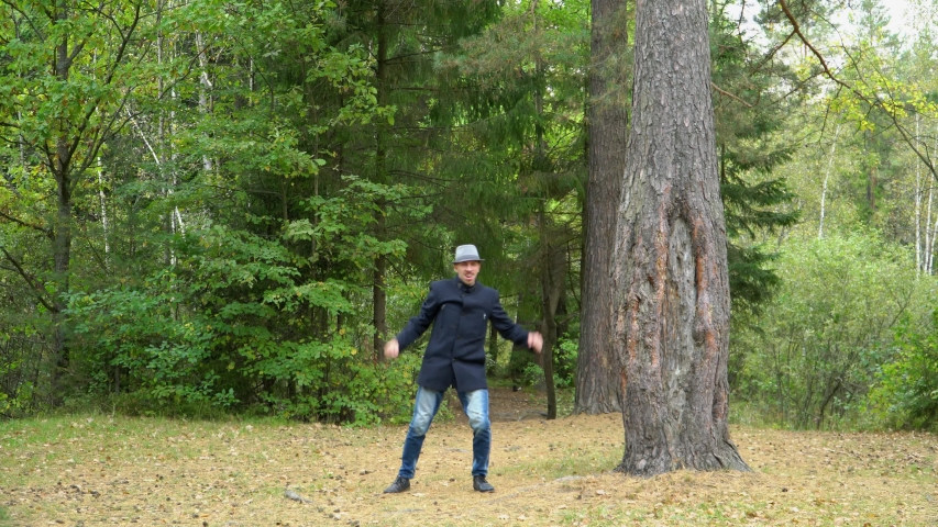 A business man in a hat and coat in the forest happily exults, actively moving his arms and legs   Shutterstock HD Video #1041457735