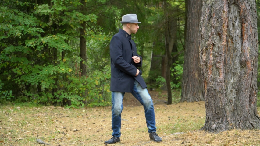 A business man in a hat and coat in the woods happily moves twisting his hands.   Shutterstock HD Video #1041457765