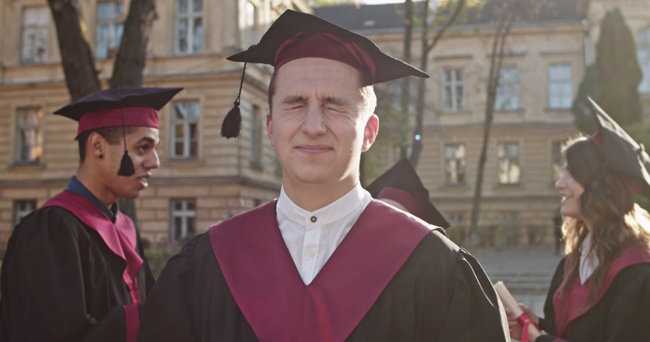 Close up of the funny young Caucasian happy male graduate in the academic cap and gown standing outside the college and smiling to the camera in bright sunlight. Portrait. | Shutterstock HD Video #1041592375