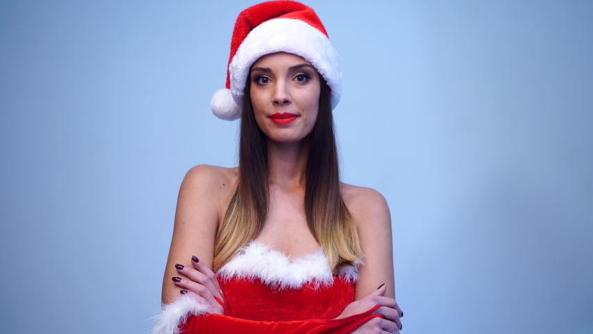 Young beautiful brunette in red dress and Santa Claus hat standing in studio on blue background smiling at the camera. Positive Christmas holiday mood. Close up portrait Santa girl flirts.  | Shutterstock HD Video #1041592645