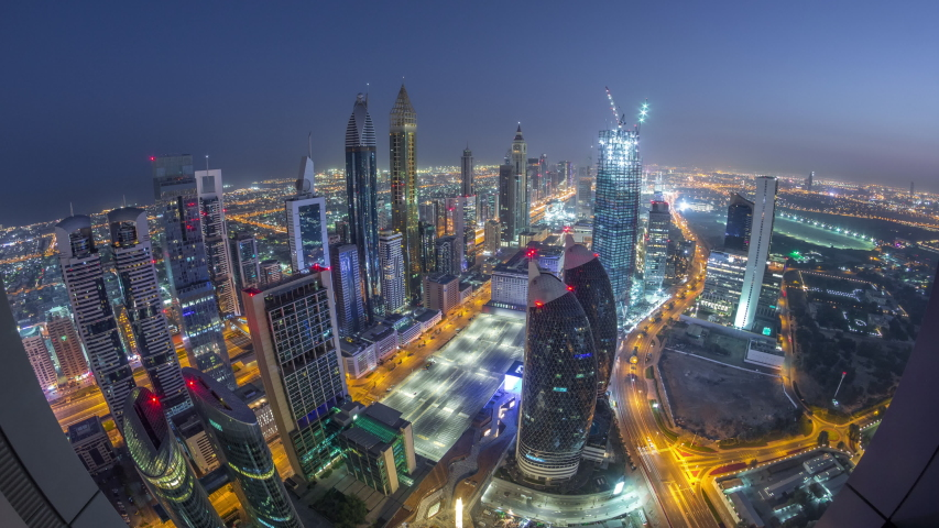 Skyline of the buildings near Sheikh Zayed Road and DIFC aerial night to day transition timelapse in Dubai, UAE. Modern towers and illuminated skyscrapers in financial center and downtown before #1041596575