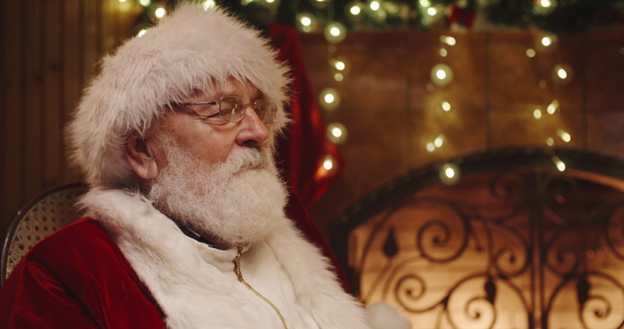 Santa claus sitting on his rocker and giving little caucasian girl a box with gift - christmas spirit, holidays and celebrations concept 4k footage | Shutterstock HD Video #1041601555
