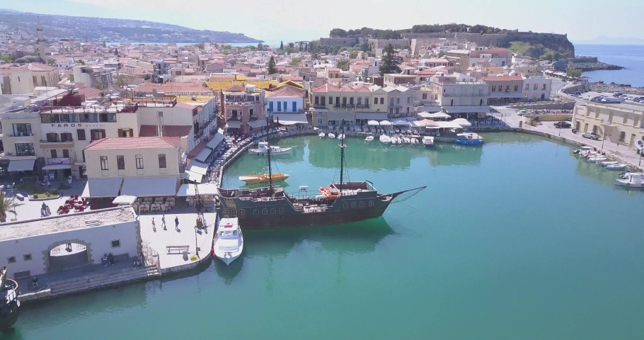 Venetian Harbour, Rethymnon, Crete, Greece – April 16 2016: The Venetian Harbor of Rethymnon, next to the modern harbor of the city, with the Egyptian lighthouse.   Shutterstock HD Video #1041631615