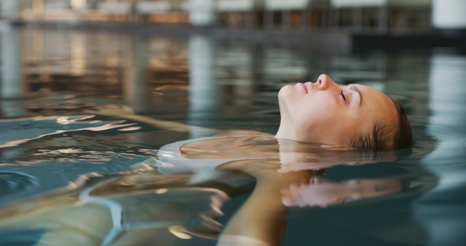 Close up of an young woman is enjoying and having relax in an indoor illuminated with night lights swimming pool in a luxury wellness center. | Shutterstock HD Video #1041780505